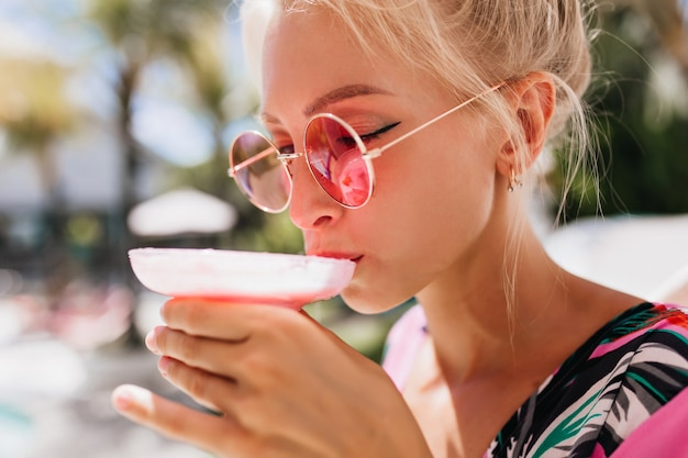 目を閉じてカクテルを飲む日焼けした女性のクローズアップの肖像画。