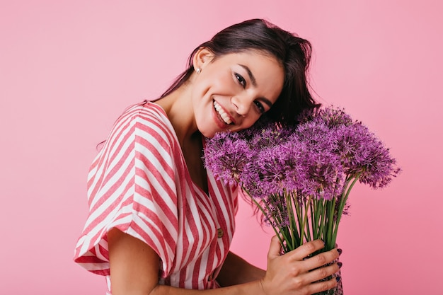 彼女の頬に魅力的なくぼみを持つ日焼けした女性のクローズアップの肖像画。女の子はかわいい笑顔で、花に頭を傾けています。