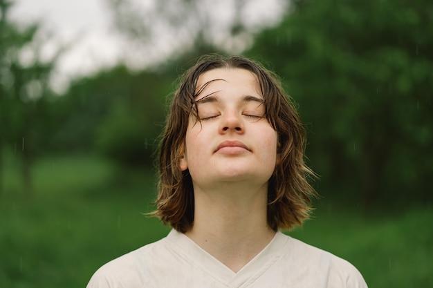 ティーンエイジャーの女の子のクローズアップの肖像画。スプレーされた小さな水しぶきまたは屋外での暖かい夏の雨からの顕著な顔を持つ幸せな陽気な十代の少女。