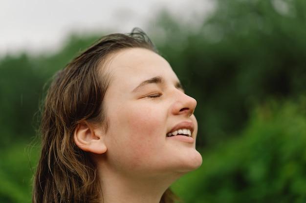 ティーンエイジャーの女の子のクローズアップの肖像画。屋外での暖かい夏の雨。