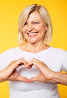 그녀는 노란색 배경에 고립 된 미소로 심장 제스처를 보여주는 동안 흰색에 부드러운 사랑스러운 금발 수석 여성의 초상화를 닫습니다