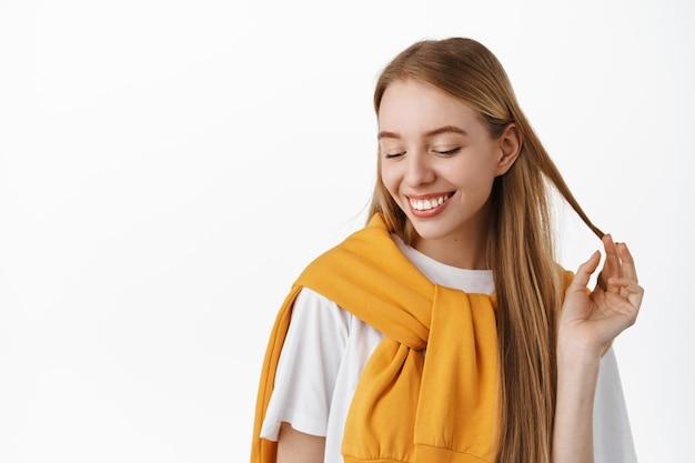 Крупным планом портрет нежной романтичной блондинки, играющей с прядью волос и избегающей зрительного контакта, кокетливой, хихикающей и краснеющей, улыбающейся белыми зубами, стоящей у стены студии