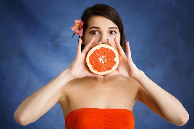 Крупным планом портрет нежного молодая женщина, держащая вырезать оранжевый над синей стеной