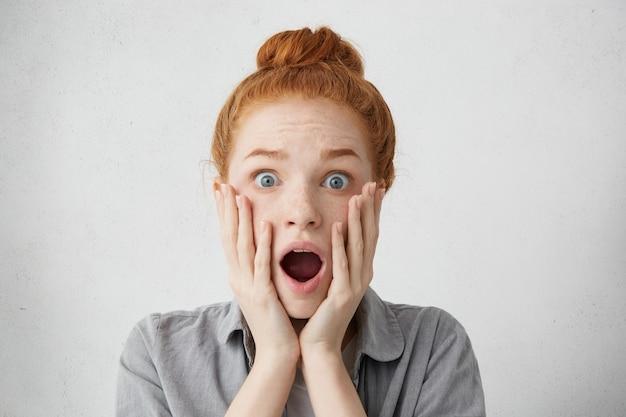 Портрет крупным планом испуганной голубоглазой женщины с рыжими бровями и волосами, смотрящей с выпученными глазами и открытым ртом, прикрывающим щеки руками, полными недоверия и удивления