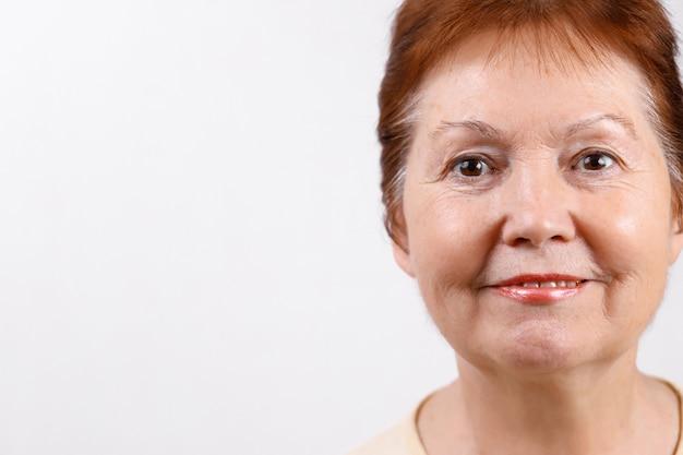 Портрет крупным планом лицо взрослой женщины на белом в легкой футболке.