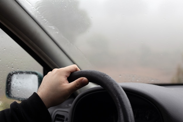 Крупным планом портрет руки до неузнаваемости человека за рулем автомобиля во время поездки в туманный и дождливый зимний день