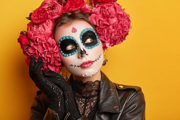 Крупным планом портрет вдумчивой женщины в творческой косметике, нарисовала улыбку, цветочный венок вокруг головы, задумчиво смотрит в сторону.
