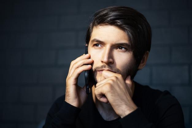 スマートフォンで話している思いやりのある若い男のクローズアップの肖像画。