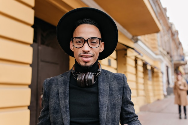 레스토랑 근처에 서 큰 헤드폰으로 피곤 된 아프리카 남성 모델의 클로즈업 초상화. 어두운 피부를 가진 잘 생긴 자신감 남자의 야외 사진.