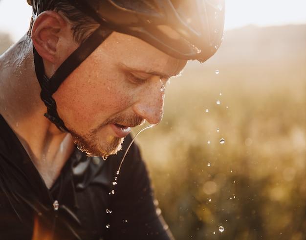 Крупным планом портрет усталого бородатого спортсмена в защитном шлеме с каплями воды на его лице.