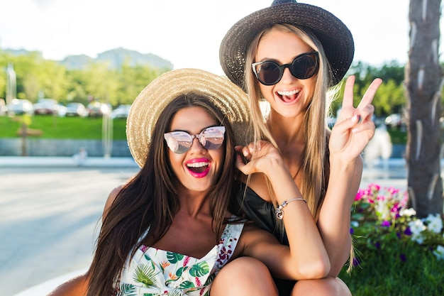 公園でカメラにポーズをとって長い髪を持つ2つの魅力的なブロンドとブルネットの女の子のクローズアップの肖像画。彼らはカメラに微笑んでいます。