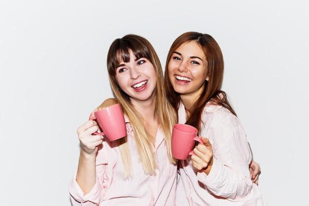 Крупным планом портрет двух веселых белых женщин в розовых пижамах с чашкой чая позирует. портрет со вспышкой.