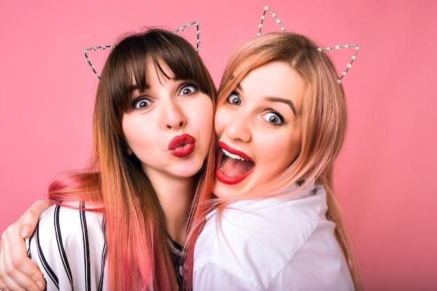 猫のパーティーヘアアクセサリー、明るいメイク、面白いクレイジーな感情、パーティーを楽しんでいる友人、ピンクの壁を身に着けている2人の幸せな出口の女性の肖像画をクローズアップ