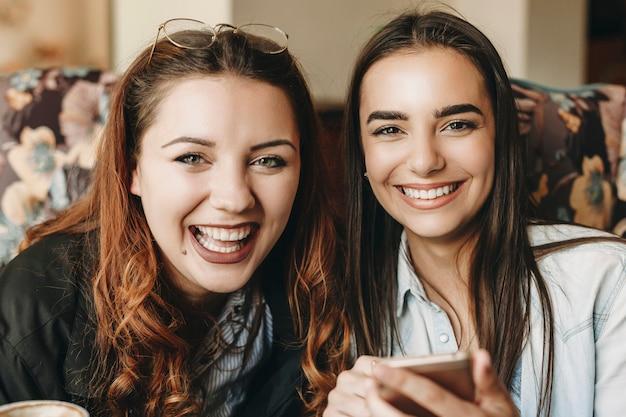 Крупным планом портрет двух прекрасных женщин, глядя на камеру, смеясь, держа смартфон, сидя в кафе.