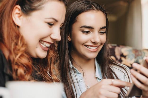 Крупным планом портрет двух прекрасных молодых подруг, хорошо проводящих время, глядя на смартфон, улыбаясь, сидя в кафе.