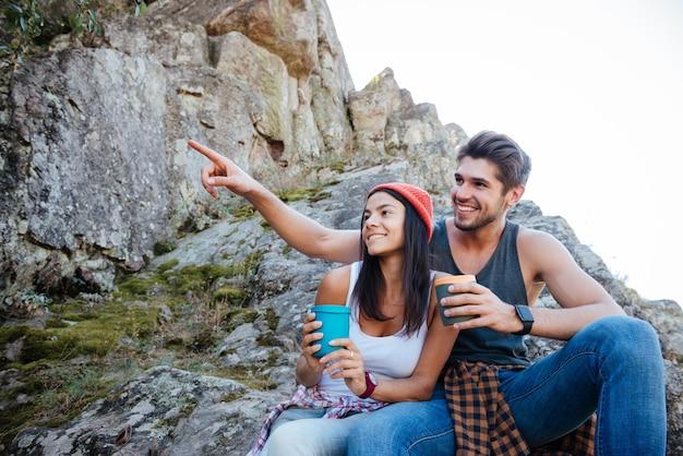 丘の上に座ってコーヒーブレイクをしている2人の若いハイカーの肖像画をクローズアップ