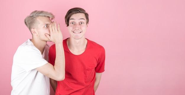 ピンクの壁に隔離された、口を大きく開いた状態で、一方が他方に秘密をささやき、ショックを受け、非常に驚いた2人の若者のクローズアップの肖像画。コピースペース付き