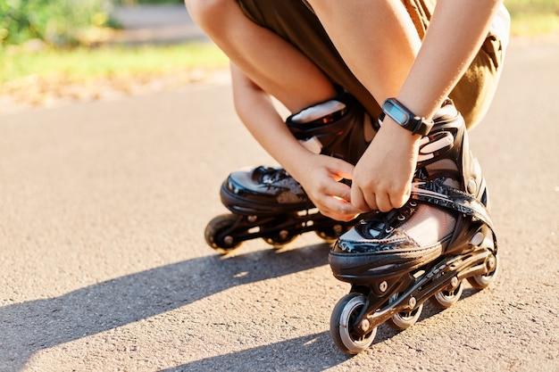 スケートをする前に、道路上の未知の子供のスクワットの肖像画をクローズアップし、ローラーブレードに靴ひもを固定します。顔のない子供は、屋外で楽しんだり、ローラーブレードをしたり、一人で遊んだりします。