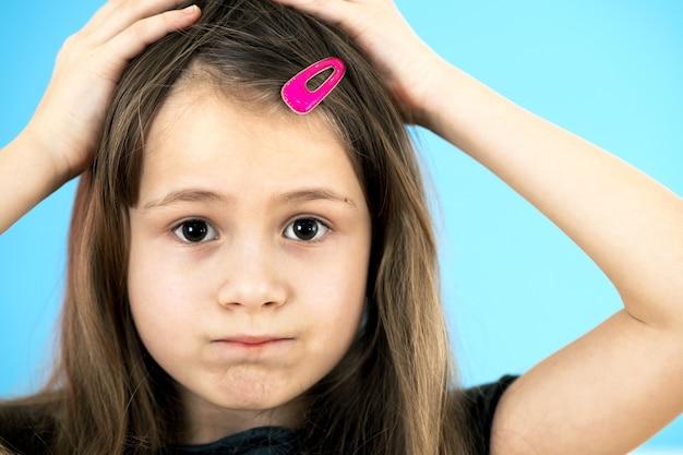 파란색 배경에 귀여운 분홍색 머리핀을 하고 화나고 생각에 잠긴 어린 소녀의 초상화를 닫습니다.