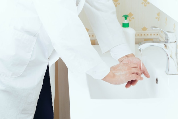 ウイルス感染を防ぐためにバスルームで手を洗う肖像画をクローズアップ