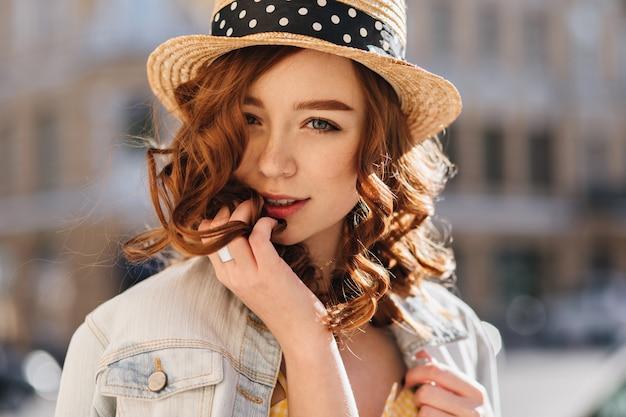 通りでポーズをとって帽子をかぶった魅力的な白人女性のクローズアップの肖像画。デニムジャケットに興味のある生姜の女の子の屋外ショット。
