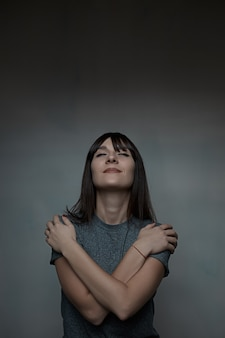 自分を抱きしめる女性の肖像画を間近します。
