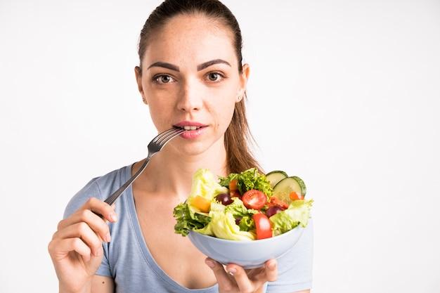 サラダを保持している女性のクローズアップの肖像画