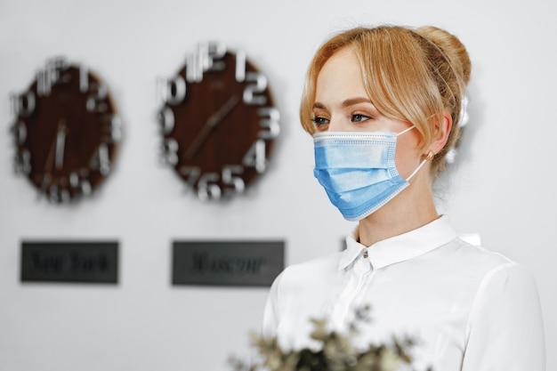 医療フェイスマスクを身に着けている女性ホテルの受付係の肖像画をクローズアップ