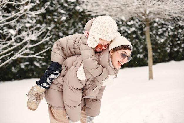 Крупным планом портрет женщины в коричневой куртке в снежном парке с дочерью