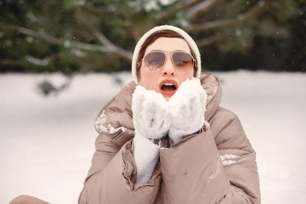 Крупным планом портрет женщины в коричневой куртке в снежном парке