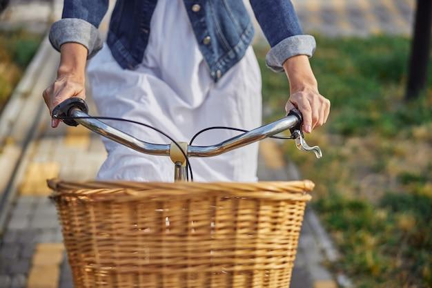 자전거로 도시 공원에서 완벽한 시간을 즐기는 데님 재킷을 입은 여성의 초상화를 클로즈업