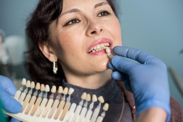 歯科医院の女性のクローズアップの肖像画。歯科医は歯の色をチェックして選択し、治療のプロセスを作ります。歯科