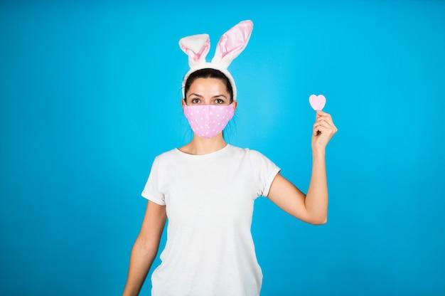 Крупным планом портрет женщины в розовой защитной маске, в ушах кролика, держащей в руке бумажное сердце на синем