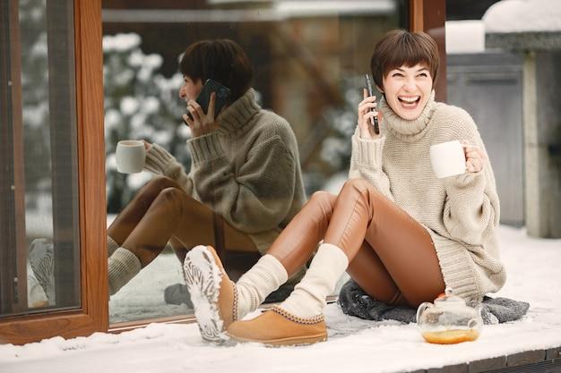 Крупным планом портрет женщины в белом свитере, пить чай и звонить