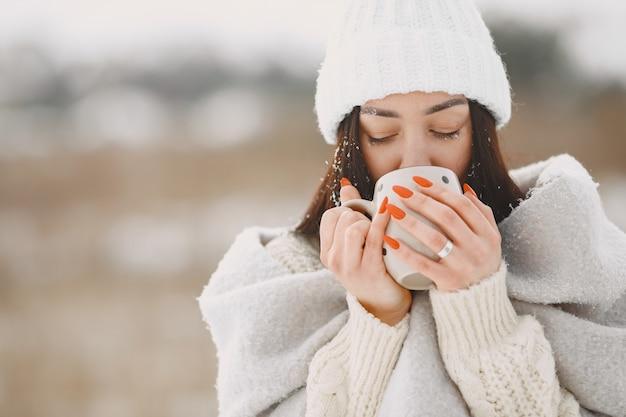 お茶と白いセーターの女性のクローズアップの肖像画