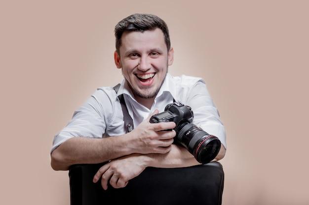 갈색 배경에 디지털 카메라로 사진을 찍는 카메라로 여자 사진 작가의 초상화를 닫습니다.