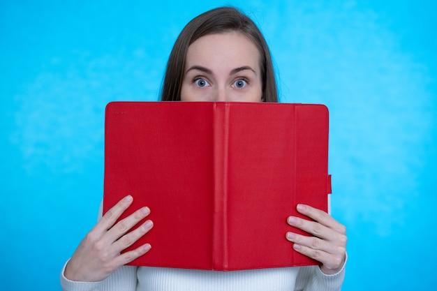 本のタスクの読書の後ろに隠れている女性の賢い賢い怖い控えめなのクローズアップの肖像画