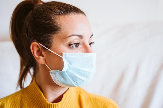 집에서 보호 마스크를 착용하는 여자의 초상화를 닫습니다. 코로나 바이러스 Covid-2019 동안 홈 컨셉을 유지하십시오 프리미엄 사진