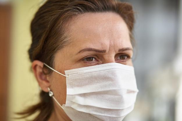 ウイルスや大気汚染のためにサージカルマスクを着ている女性の肖像画を間近します。