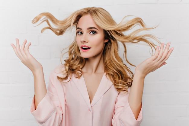 Крупным планом портрет чудесной дамы играет со своими длинными светлыми волосами. внутреннее фото потрясающей европейской женской модели в розовой пижаме, изолированной на белой стене.
