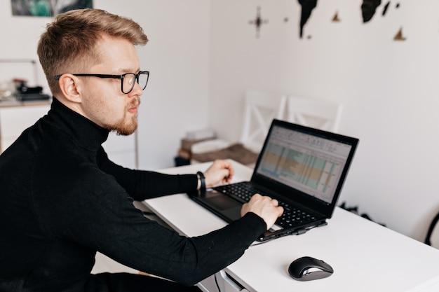 白いモダンなホームオフィスで働く若い男の肖像画を間近します。ハンサムなオフィスの男の屋内ポートレート