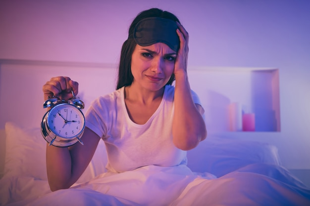 침대에 앉아 머리 통증을 겪고 걱정 아픈 슬픈 여자의 클로즈 업 초상화