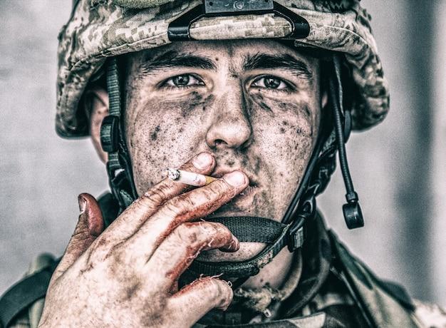 상처 입은 군인, 더러운 얼굴을 가진 미국 해병, 피가 묻은 담배를 들고 담배를 피우는 초상화를 닫습니다. 현장 작업 후 쉬고있는 군 위생병. 외상성 전쟁 경험