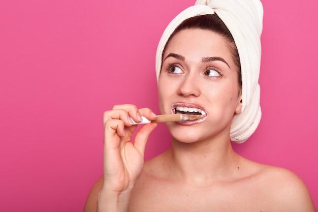 白いタオルを身に着けている彼女の歯を磨く若い愛らしい女性の肖像画を閉じる