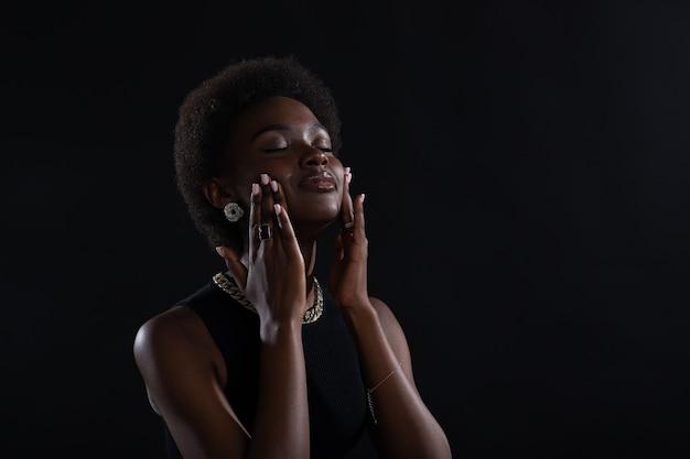 Крупным планом портрет молодой афро-американской чернокожей женщины, занимающейся фейсбилдингом йоги, лицо, гимнастика, йога, самомассаж щеки.