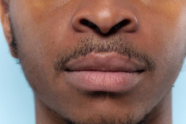 若いアフリカ系アメリカ人の男の肖像画をクローズアップ。人間の感情、顔の表情、広告、販売、または男性の美容と健康の概念。