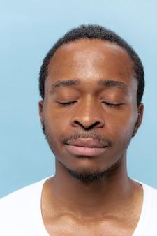 青い背景に白いシャツを着た若いアフリカ系アメリカ人の男の肖像画を閉じます。人間の感情、表情、広告、販売コンセプト。落ち着いて見えます。目を閉じて立って夢を見ている。