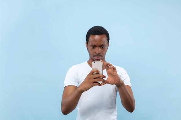 白いシャツを着た若いアフリカ系アメリカ人男性の肖像画をクローズアップ..彼のスマートフォンで写真やvlogコンテンツを撮る。
