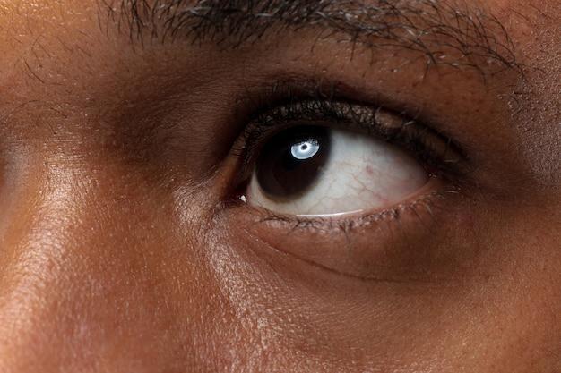 파란색 배경에 젊은 아프리카 계 미국인 남자의 초상화를 닫습니다. 인간의 감정, 표정, 광고, 판매 또는 미용 개념. 눈이 뜨겁다. 차분하고 위를 올려다 본다.