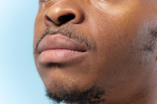 青い背景の上の若いアフリカ系アメリカ人の男の肖像画を閉じます。人間の感情、顔の表情、広告、販売、または男性の美容と健康の概念。唇の写真撮影。落ち着いて見えます。